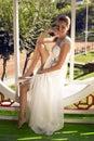 Beautiful smiling bride in elegant wedding dress posing in garden Royalty Free Stock Photo