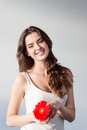Beautiful smiling caucasian brunette woman white singlet holding red flower over gray background Stock Images