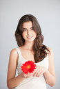 Beautiful smiling caucasian brunette woman white singlet holding red flower over gray background Royalty Free Stock Image
