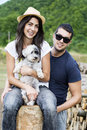 Beautiful smiling couple hugging their white dog outdoor young having fun with in the mountain Royalty Free Stock Photos