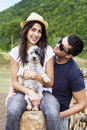 Beautiful smiling couple hugging their white dog outdoor young having fun with in the mountain Stock Photography