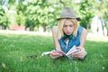 Beautiful smiling dark haired young woman lying on grass and reading book against summer green park Royalty Free Stock Photo