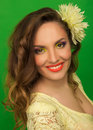 Beautiful smiling girl with bright up make up and with a flower in her hair on green background Stock Photos