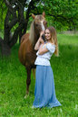 Beautiful smiling girl embraces bay horse in apple orchard Royalty Free Stock Photo