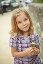 Beautiful smiling girl holding flower little summer in city park Stock Image