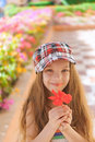 Beautiful smiling girl holding red flower little summer in city park Royalty Free Stock Photos