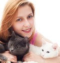 Beautiful smiling girl hugging her two cats Royalty Free Stock Photography
