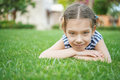 Beautiful smiling girl lies on green grass little summer in city park Royalty Free Stock Image