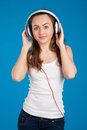 Beautiful smiling girl listening music wearing white headphones studio over blue background Royalty Free Stock Photos