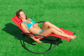 Beautiful smiling girl lying in a deck chair with his eyes closed Royalty Free Stock Photography