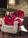A beautiful smiling girl in red Christmas home clothes pajamas and white home boots sits in a chair against the background of th
