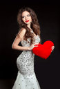 Beautiful smiling girl with red heart in luxury dress isolated o Royalty Free Stock Photo