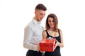 Beautiful smiling girl takes red gift that has brought young charming guy