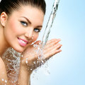 Beautiful smiling girl under splash of water Royalty Free Stock Photo