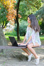Beautiful smiling happy girl using notebook in summer park Royalty Free Stock Photo