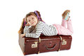 Beautiful smiling little girl laying on retro suitcase