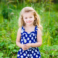 Beautiful smiling little girl with long blond curly hair and flower in her hands outdoor portrait in summer park on bright sunny Stock Photos