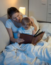 Beautiful smiling mother reading story to her baby boy before go Royalty Free Stock Photo