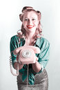 Beautiful smiling pinup woman holding retro turn dial phone contact us concept Royalty Free Stock Image
