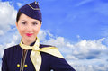 Beautiful smiling stewardess on a background sky Stock Image