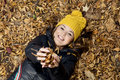 Beautiful smiling teenage girl lying in the autumn leaves with yellow cap Stock Images