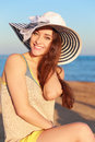Beautiful smiling woman in hat on beach background Stock Photo