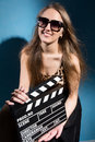 Beautiful red-haired woman holding a movie clapper, isolated ove