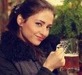 Beautiful smiling woman holding mug of lager beer. Closeup portrait