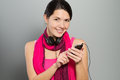 Beautiful smiling woman listening to music standing with her headphones around her neck as she checks the downloaded tunes on her Royalty Free Stock Images