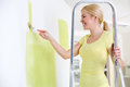 Beautiful smiling woman painting wall young in her new home while standing on ladder Stock Image