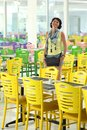 Beautiful smiling woman and posing for the camera among the multi-colored chairs.