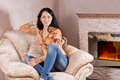 Beautiful smiling woman relaxing her jeans stylish top comfortable upholstered armchair front warm fire Royalty Free Stock Photo