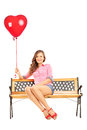 Beautiful smiling woman sitting on a bench and holding a red hea heart balloon isolated white background Stock Image