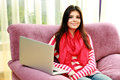 Beautiful smiling woman sitting on the sofa with laptop young at home Royalty Free Stock Photos