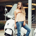 Beautiful smiling woman standing in front of classic moped motorcycle ready to ride. Royalty Free Stock Photo
