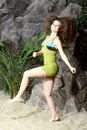 Beautiful smiling woman in swimsuit goes near gray rocks and green jersey Royalty Free Stock Photography