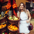 Beautiful smiling young adult woman standing near street fruit store with tropical fruits in baskets. Royalty Free Stock Photo