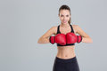Beautiful smiling young fitness woman wears red boxing gloves