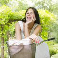 Beautiful smiling young woman with bicycle portrait of in the park Stock Photo
