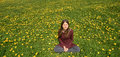 Beautiful smiling young woman relaxing on a meadow with many dandelions in the spring sun. Frontal view with copyspace. Royalty Free Stock Photo