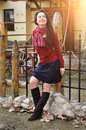 Beautiful smiling young woman in scarf red pullover posing alone against yard and sunset light.