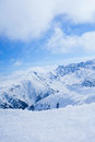 Beautiful snow capped mountains against the blue sky high under in winter Royalty Free Stock Image