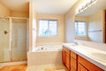 Beautiful soft tones bathroom with shower and whirlpool ivory beige tile floor wood cabinets glass door accomplish each other Stock Photo