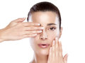 Beautiful spa girl face skincare concept woman with hands on her covering one eye perfect skin nude makeup portrait isolated on Stock Images