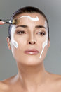 Beautiful spa girl skincare concept woman applying a treatment with cream on her face perfect skin nude makeup Royalty Free Stock Photos