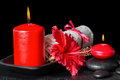 Beautiful spa still life of red hibiscus flower with dew, candle