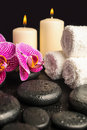 Beautiful spa still life of zen stones with drops blooming twig stripped violet orchid phalaenopsis and stacked towel and Stock Images