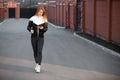 Beautiful sporty girl using device walking in the street