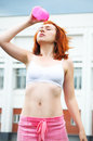 Beautiful sporty red-haired girl drinking and pouring the water after sports Royalty Free Stock Photo