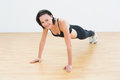 Beautiful sporty woman doing push ups in fitness studio portrait of a young Royalty Free Stock Image